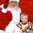 サンタさんに抱っこされながら「助けて」とサインを送る赤ちゃん